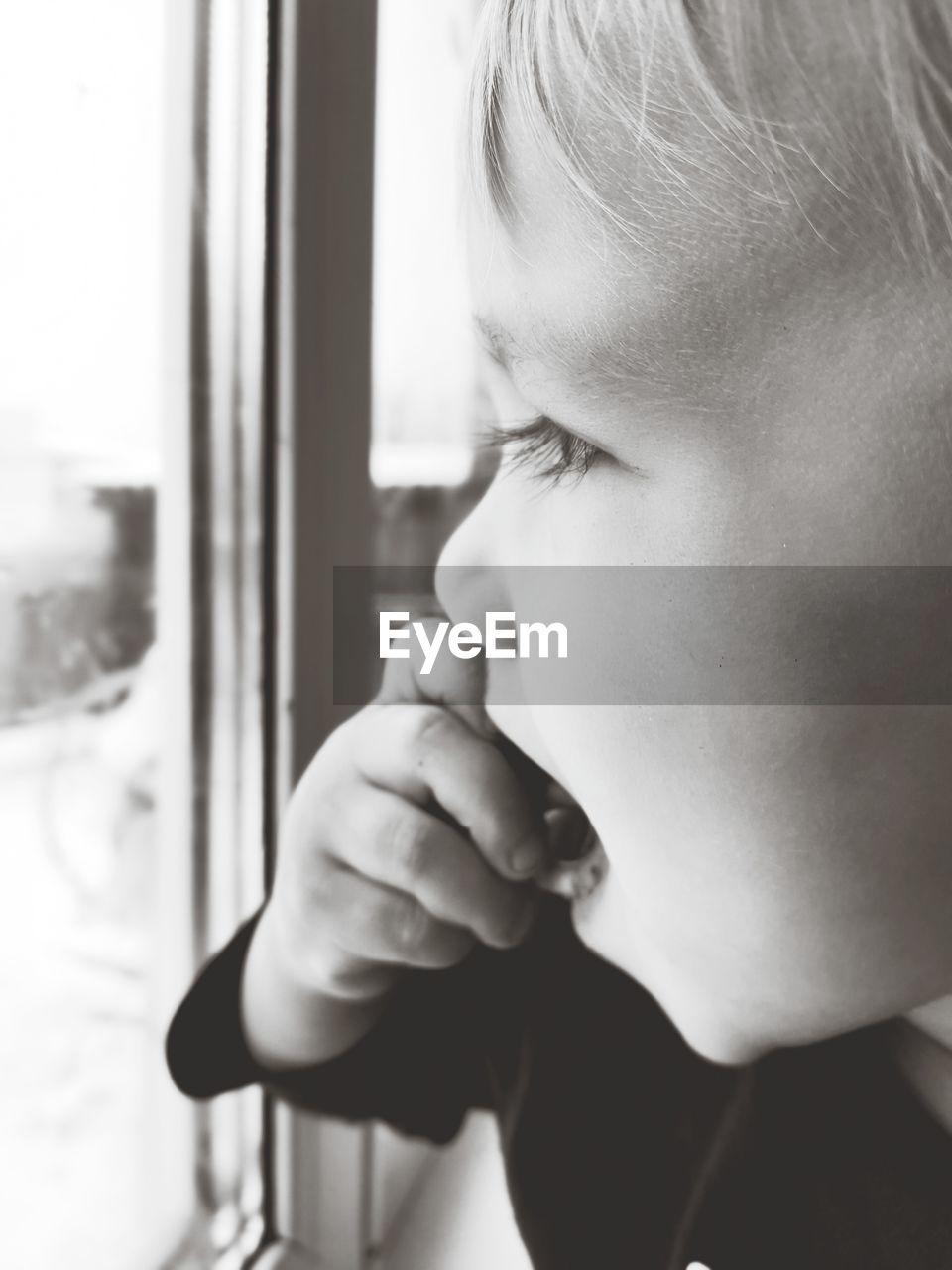 Close-up portrait of boy looking through window