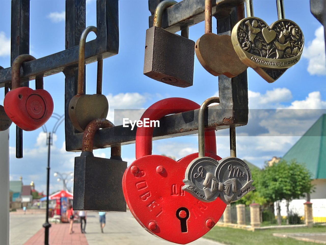 Various Padlocks Hanging On Railing Against Sky During Sunny Day