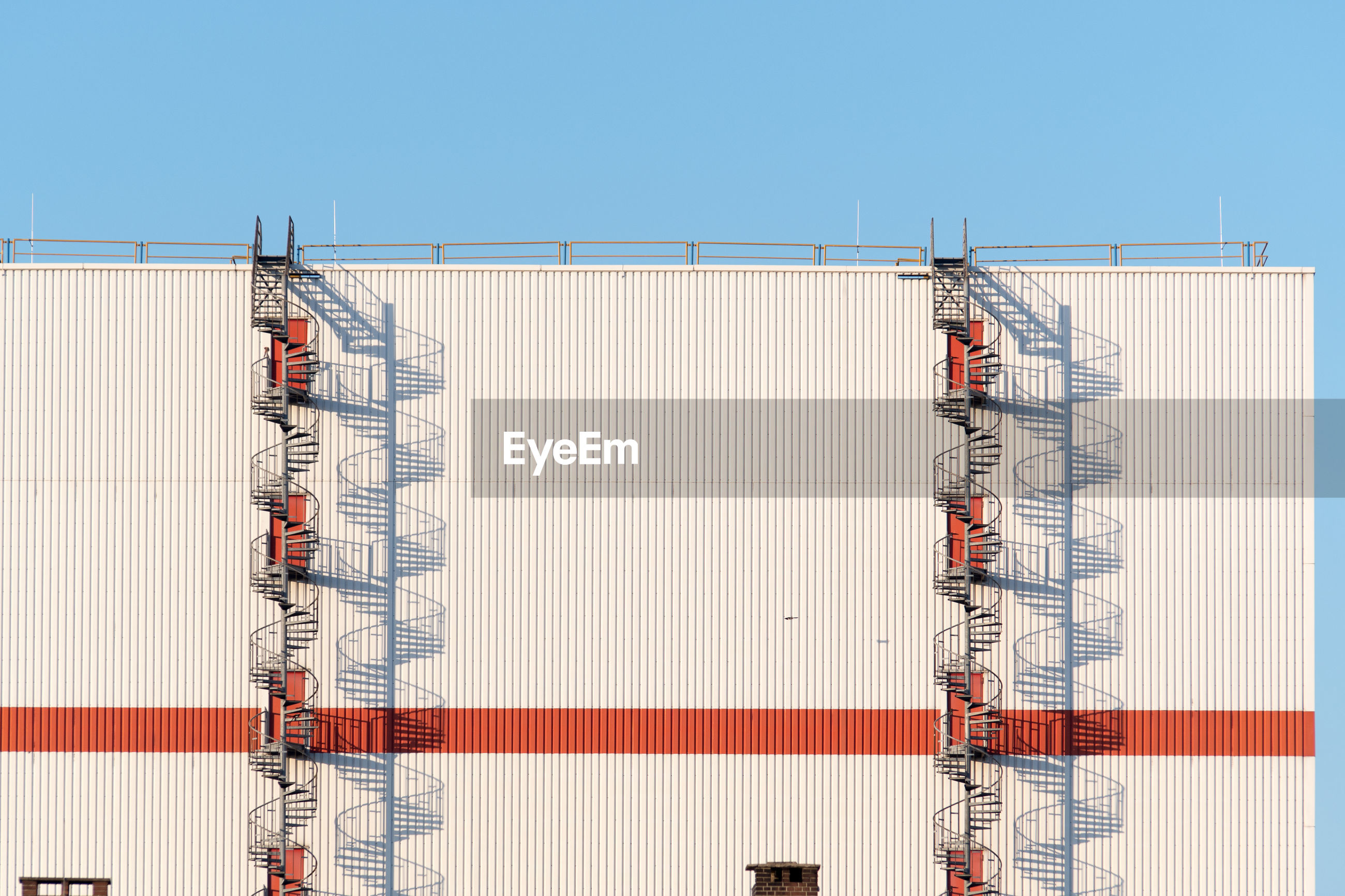 Fire escape on metallic structure against clear blue sky