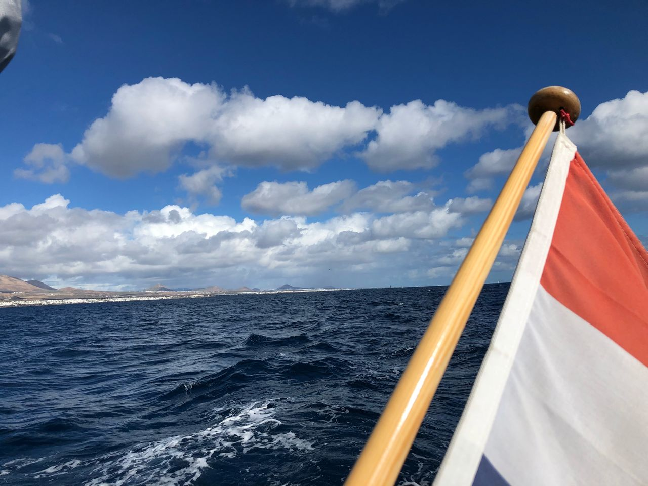 sea, sky, water, cloud - sky, flag, nautical vessel, horizon over water, horizon, mode of transportation, nature, day, no people, transportation, beauty in nature, scenics - nature, patriotism, outdoors, sailing, motion, sailboat