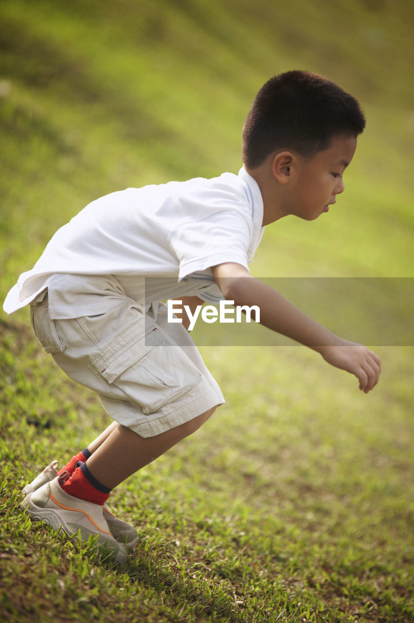 Side View Of Boy Standing On Grassy Field While Playing At Park