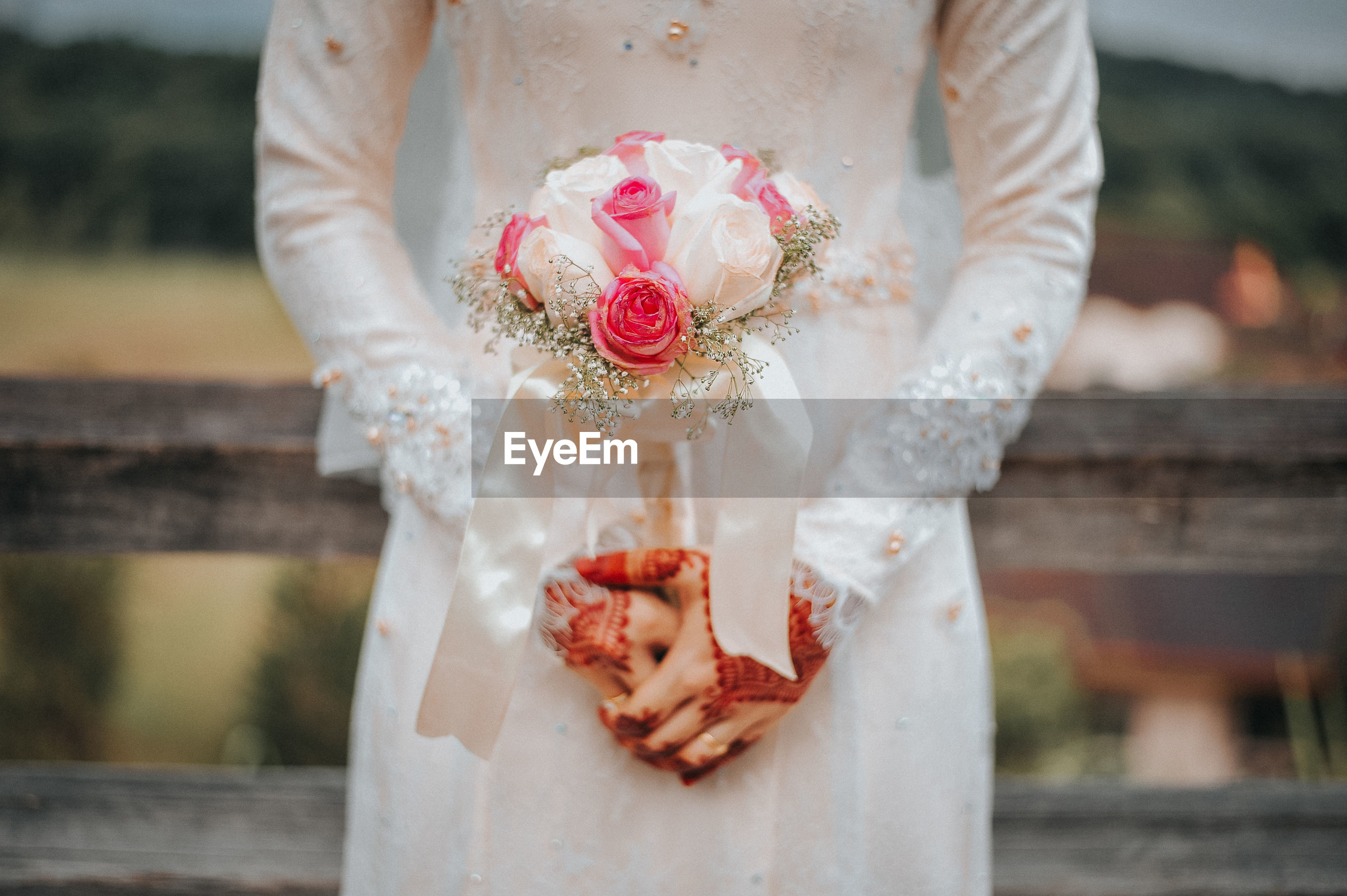 Midsection of bride holding bouquet during wedding