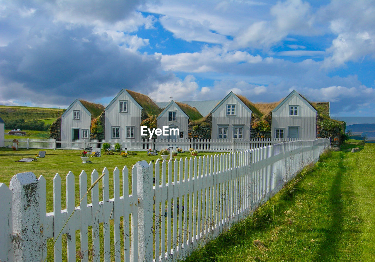 architecture, built structure, cloud - sky, building exterior, sky, grass, fence, barrier, building, boundary, plant, nature, day, house, security, picket fence, no people, safety, land, protection, outdoors