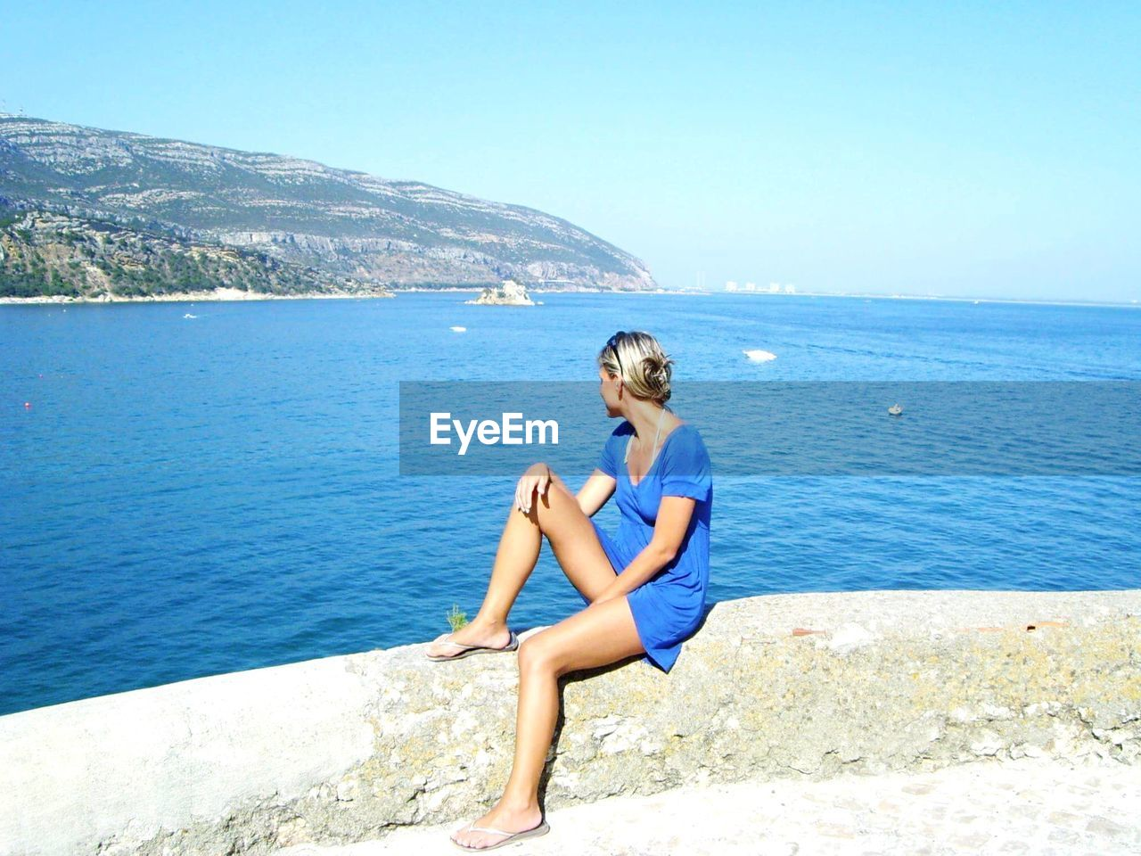 Side view of mid adult woman looking at sea while sitting on retaining wall against sky during sunny day