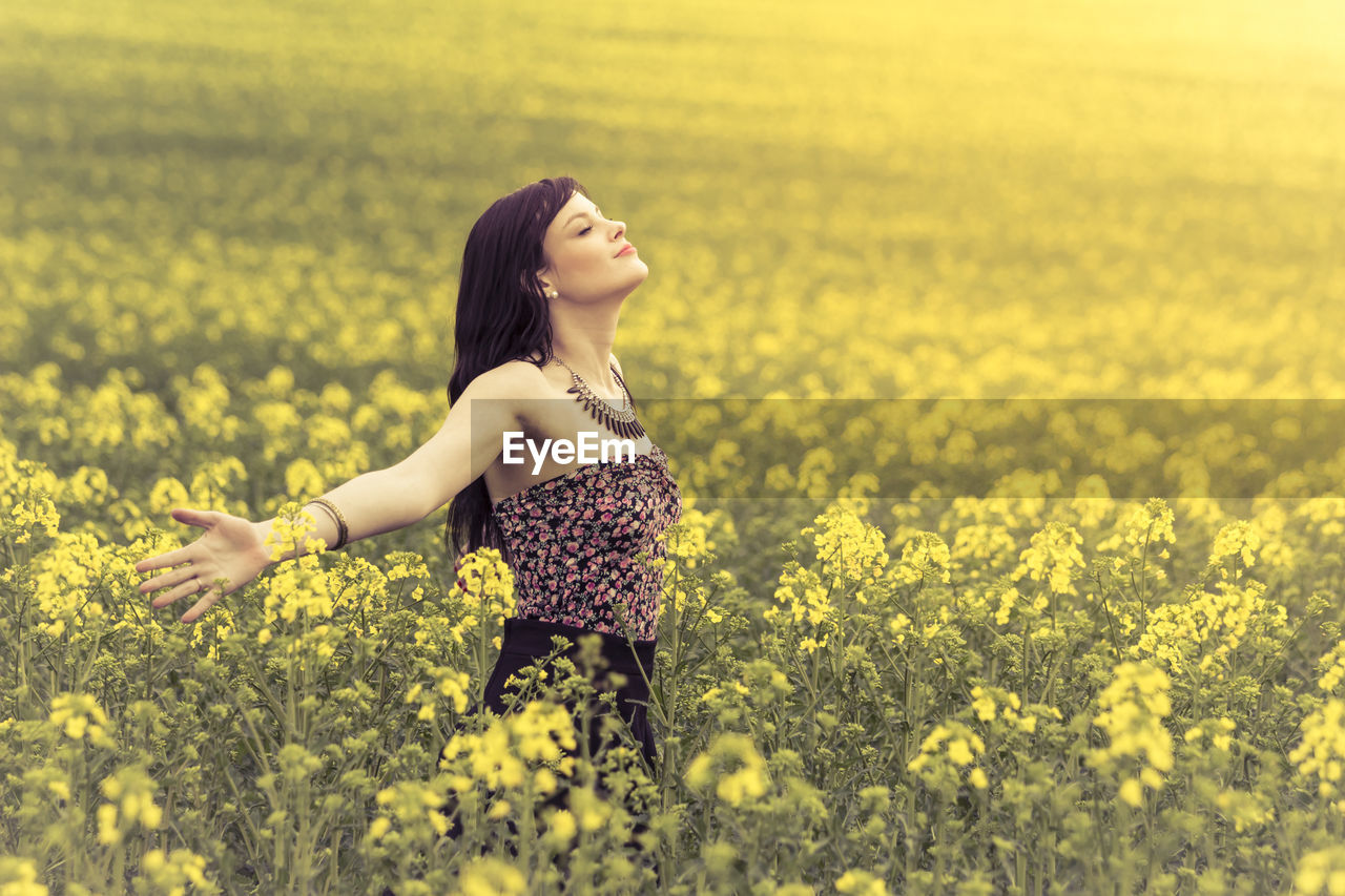 Beautiful Woman With Arms Outstretched Standing On Flowering Field