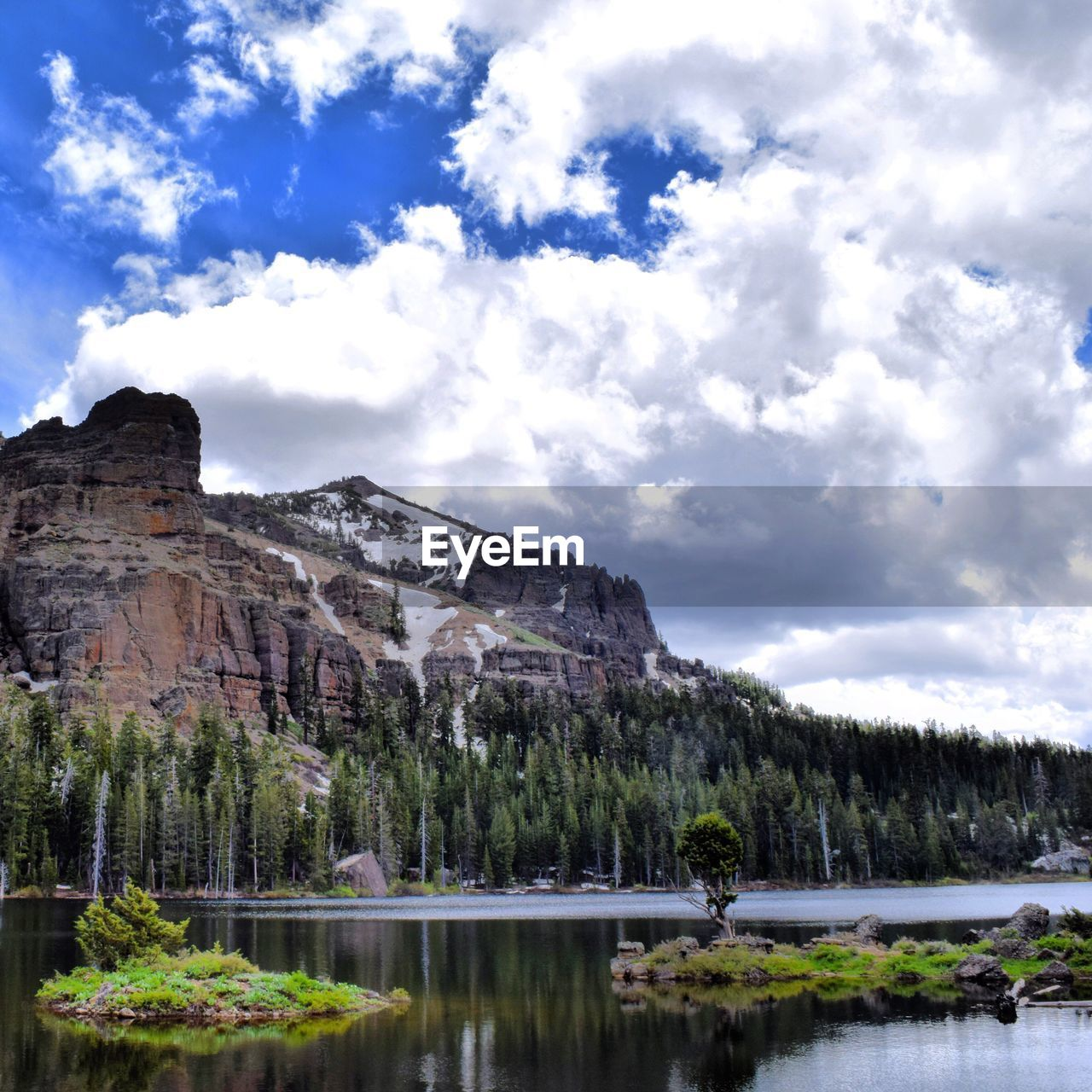 Scenic View Of Lake By Mountain Against Cloudy Sky