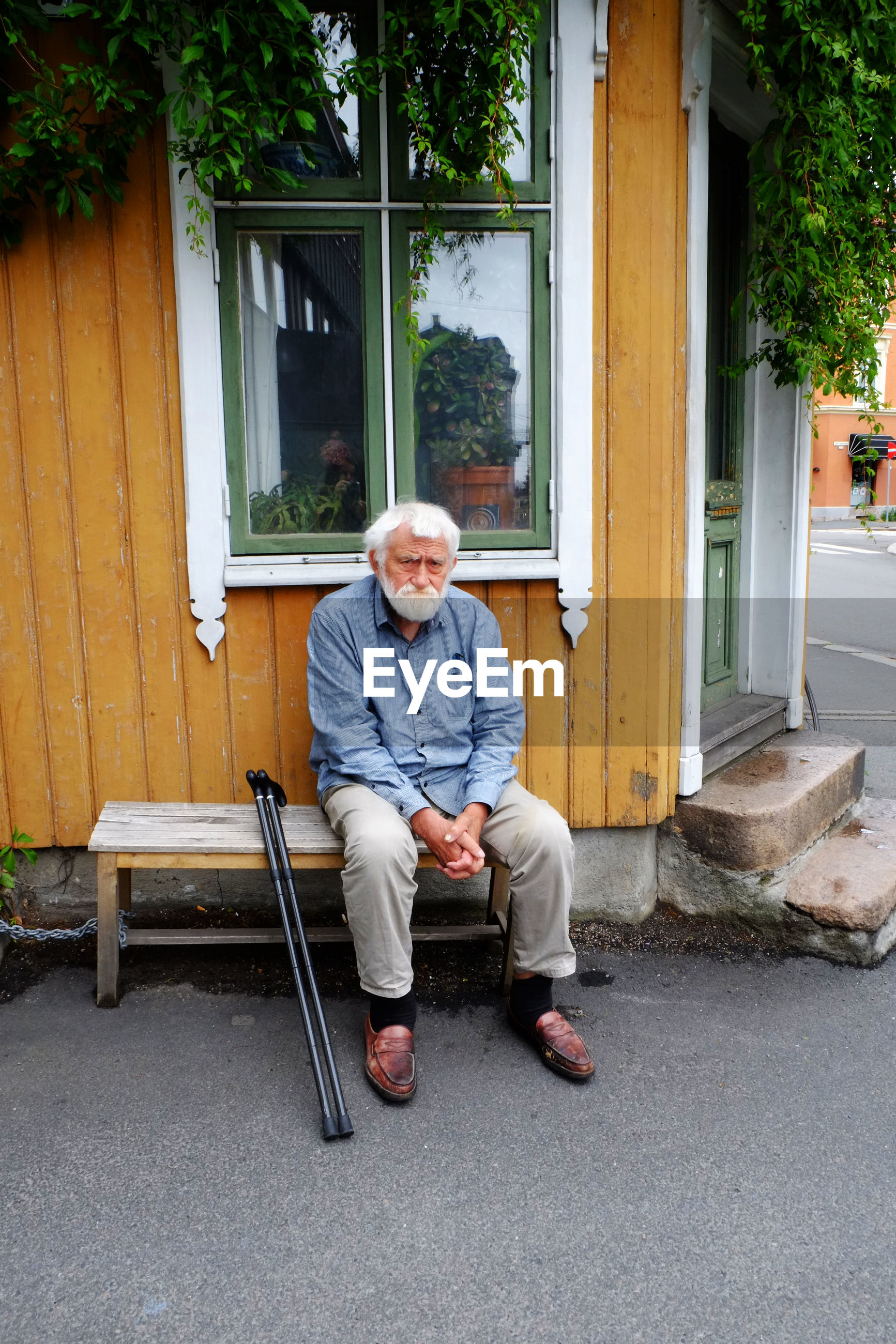 Full length of senior man sitting on bench by house