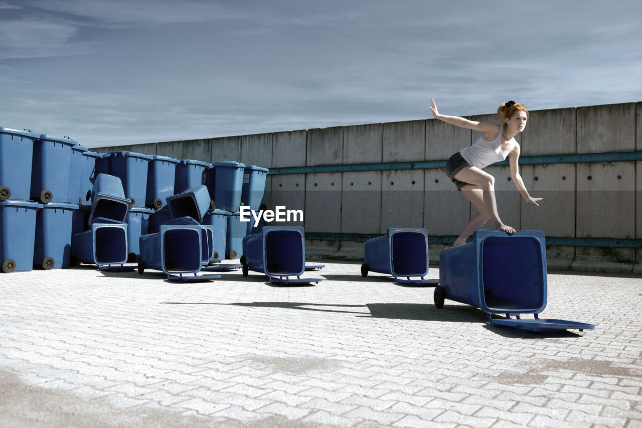 Young woman jumping on garbage bins