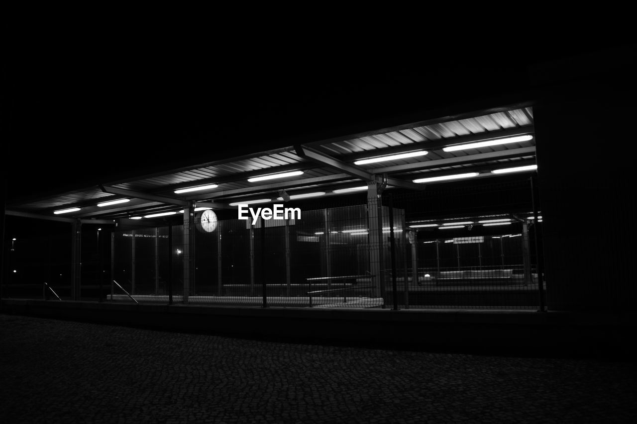 night, illuminated, rail transportation, transportation, architecture, lighting equipment, no people, built structure, copy space, public transportation, dark, railroad station platform, train, outdoors, absence, in a row, railroad station, nature, sky, station, ceiling