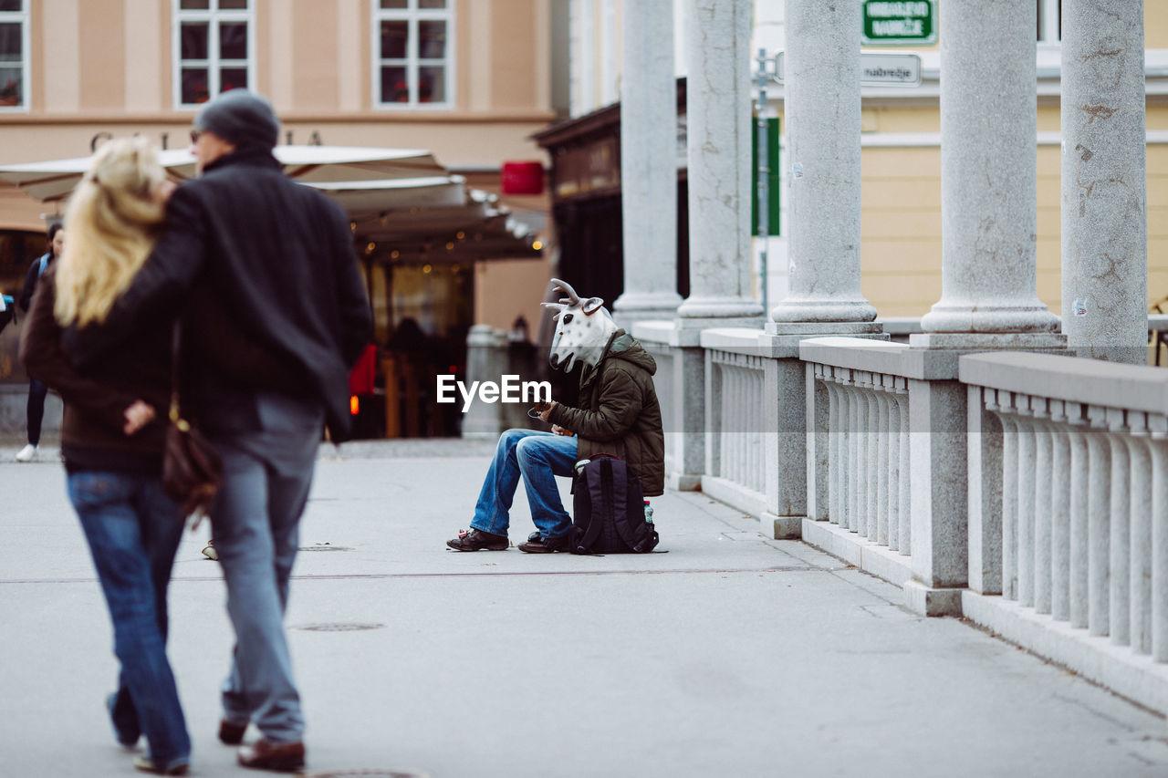 REAR VIEW OF PEOPLE WALKING ON SIDEWALK
