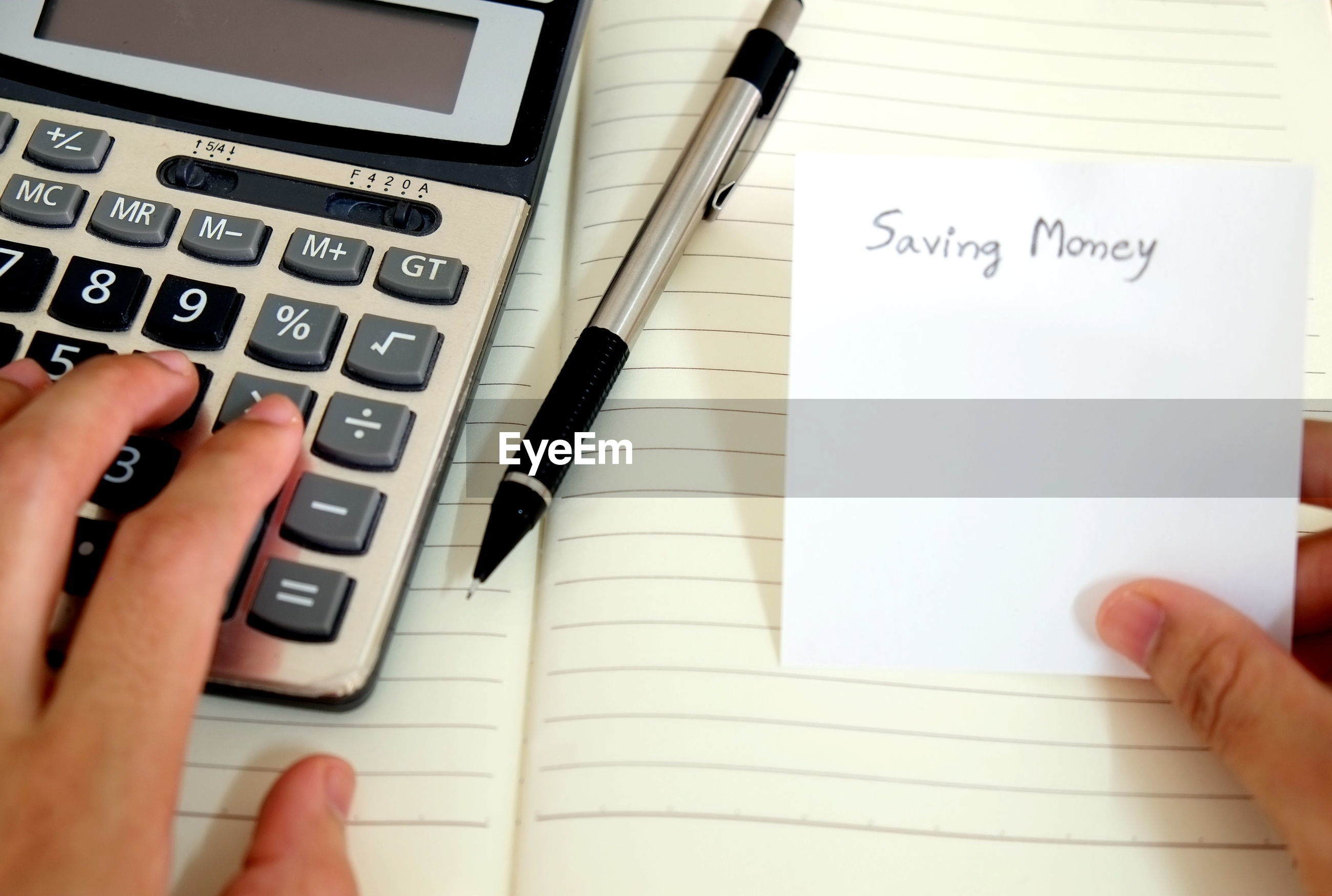 Cropped hands with message and calculator on book