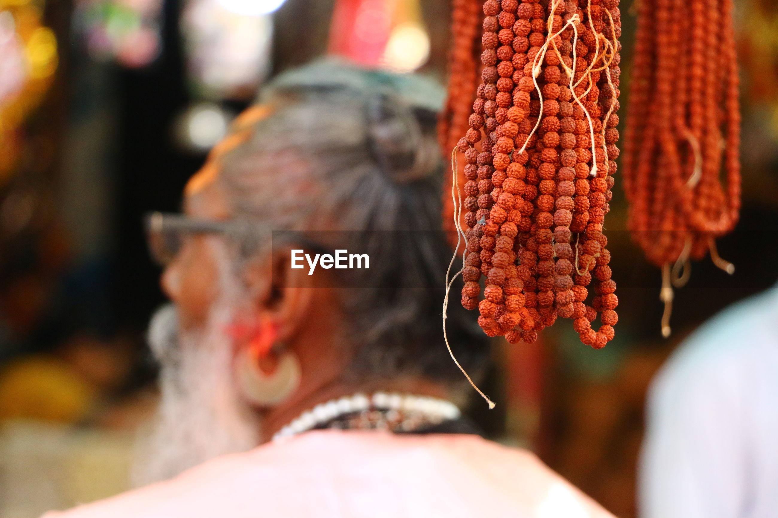 Close-up of rudraksha hanging at market stall with sadhu in background
