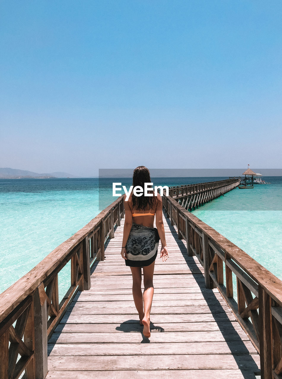 Rear view of woman walking on pier over sea against clear sky
