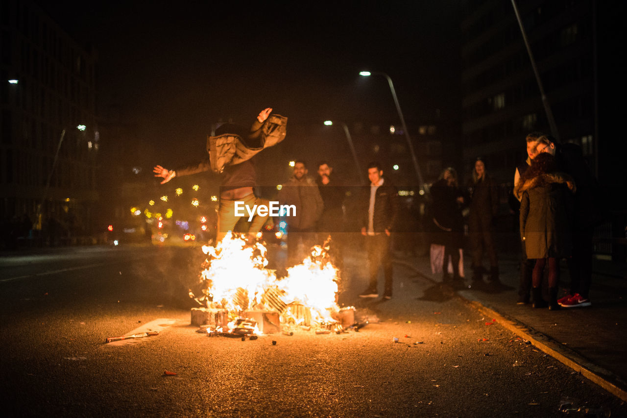 night, burning, flame, real people, fire, heat - temperature, fire - natural phenomenon, group of people, illuminated, motion, men, lifestyles, glowing, street, city, people, leisure activity, arts culture and entertainment, women, performance, outdoors, sparkler, bonfire, firework - man made object