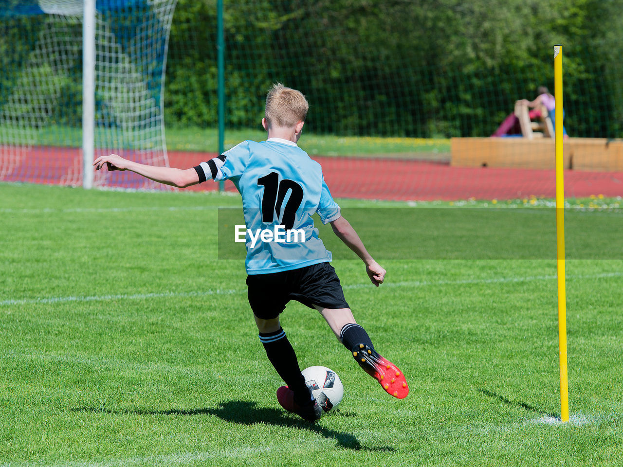 Rear View Of Boy Playing Soccer At Grassy Field