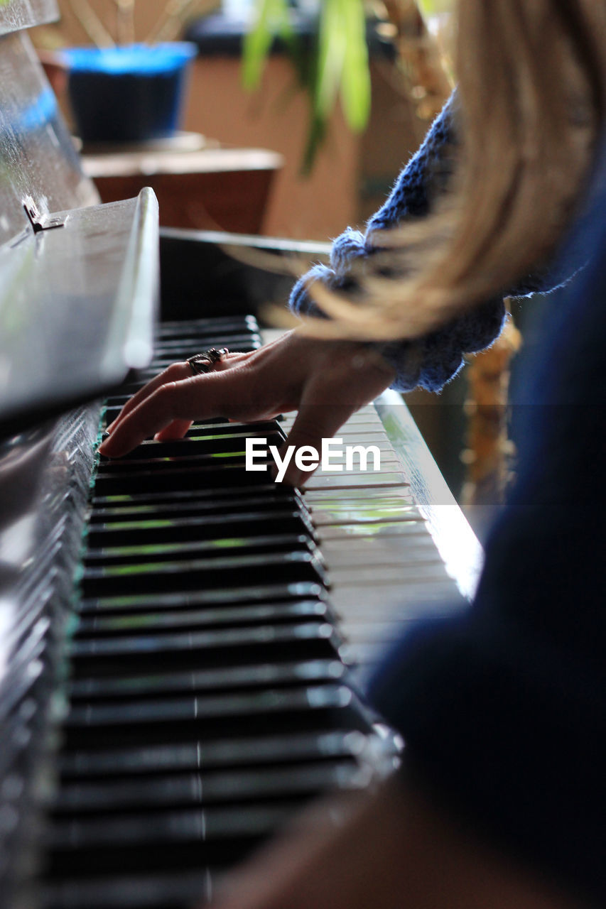 Close-up side view of hand playing the piano
