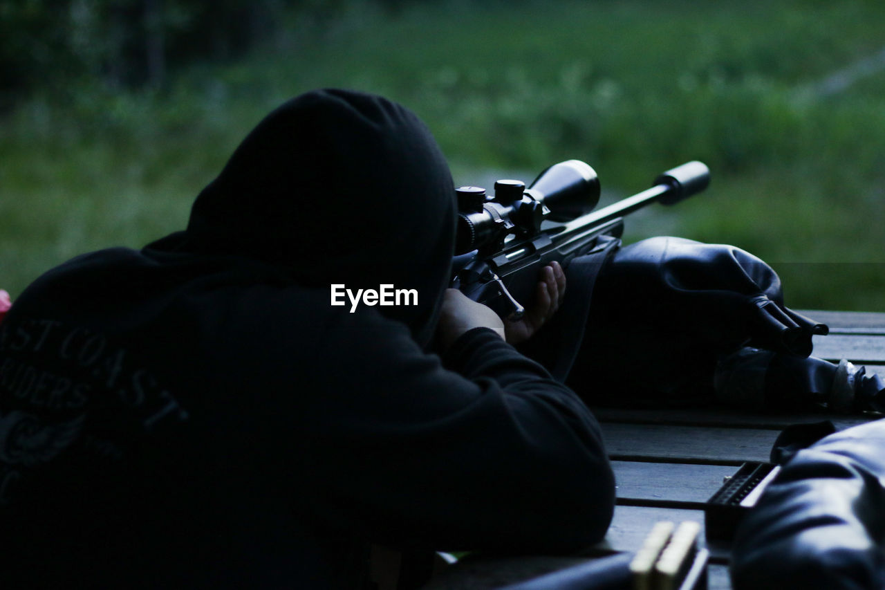 one person, men, gun, real people, rifle, holding, aiming, rear view, leisure activity, weapon, day, concentration, headshot, sport, outdoors, shooting a weapon, skill, lifestyles, hunting, hunter, aggression