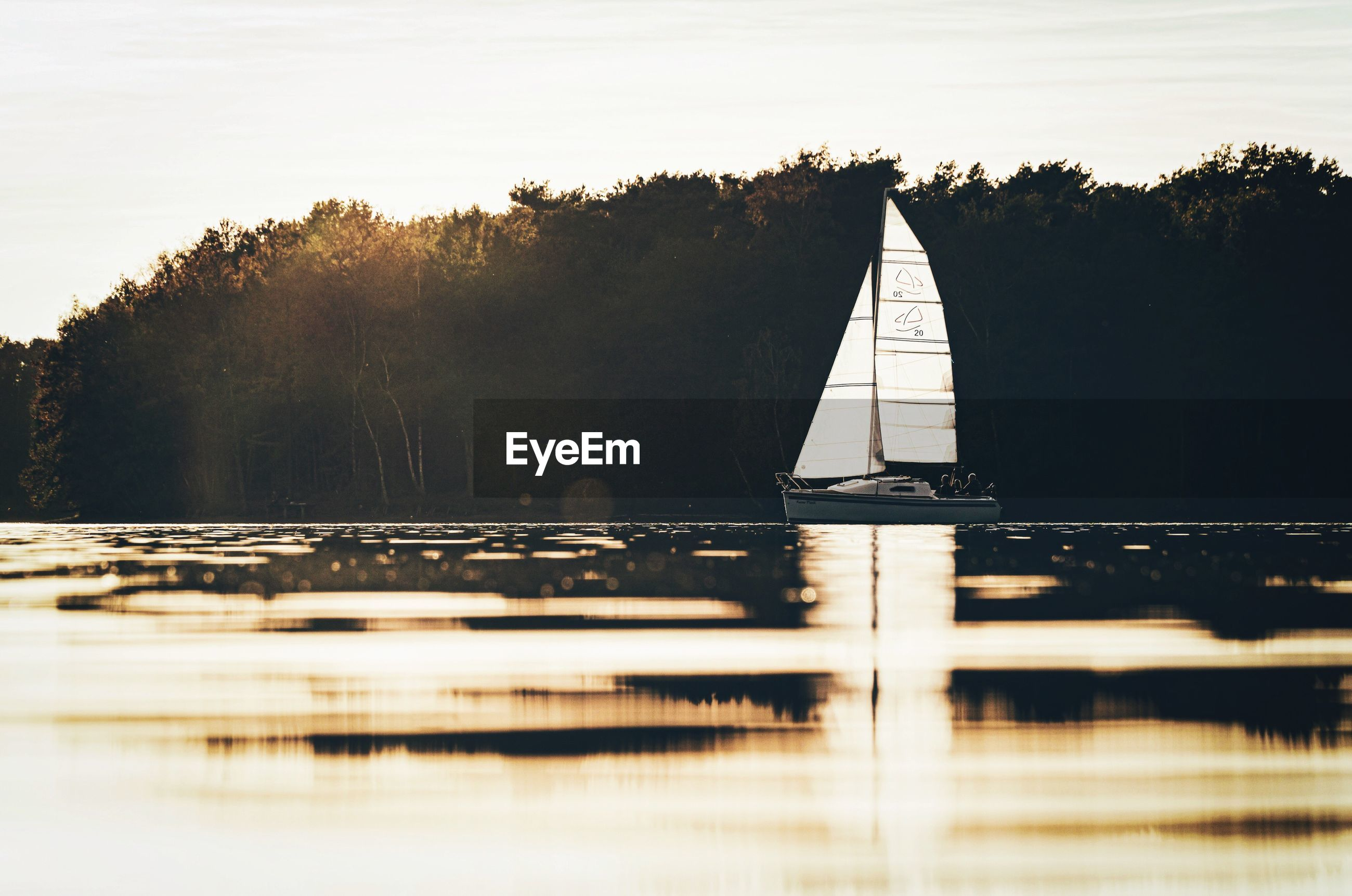 Scenic view of lake with boat against sky during sunset