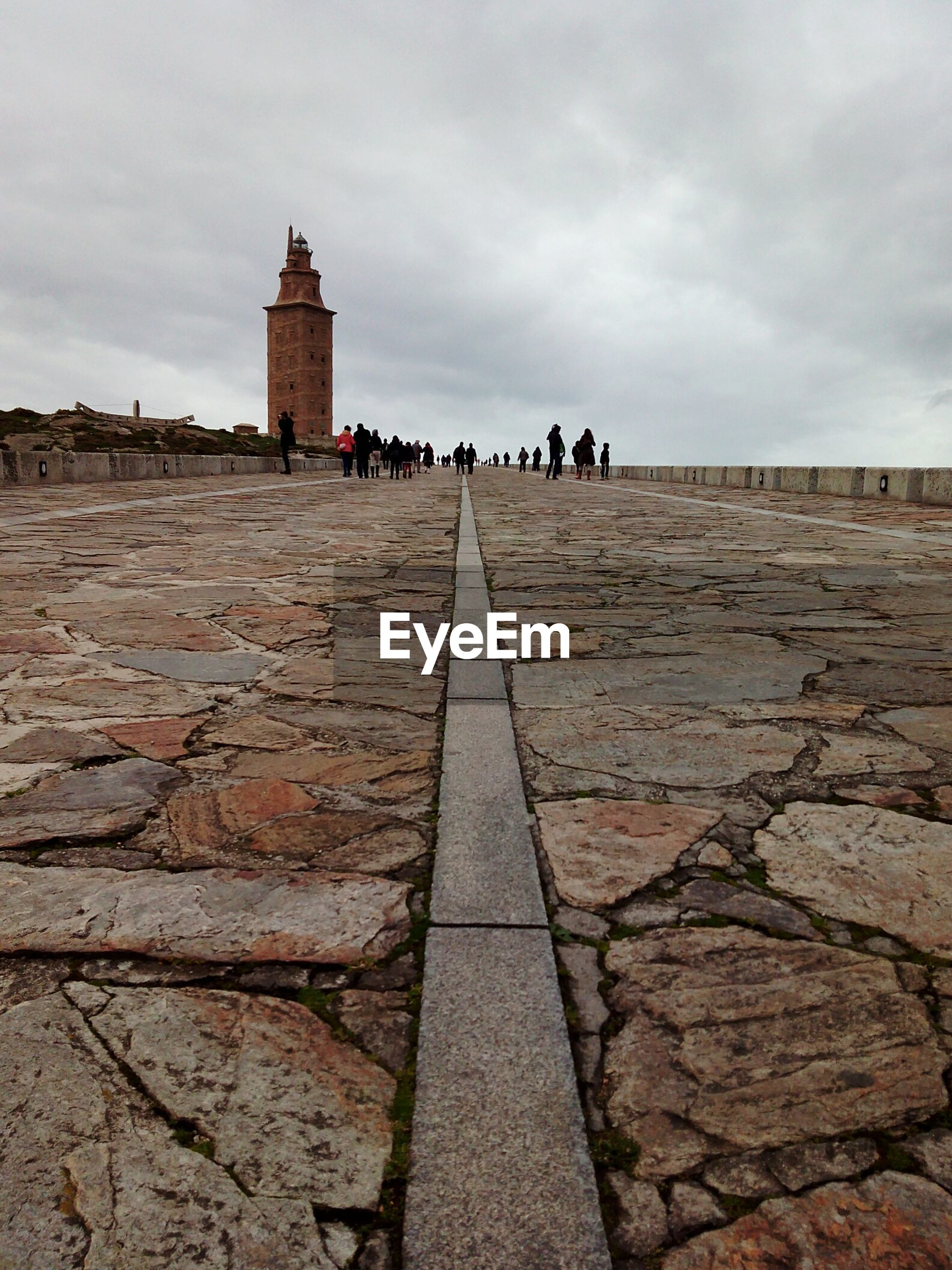 People on walkway at tower of hercules against sky