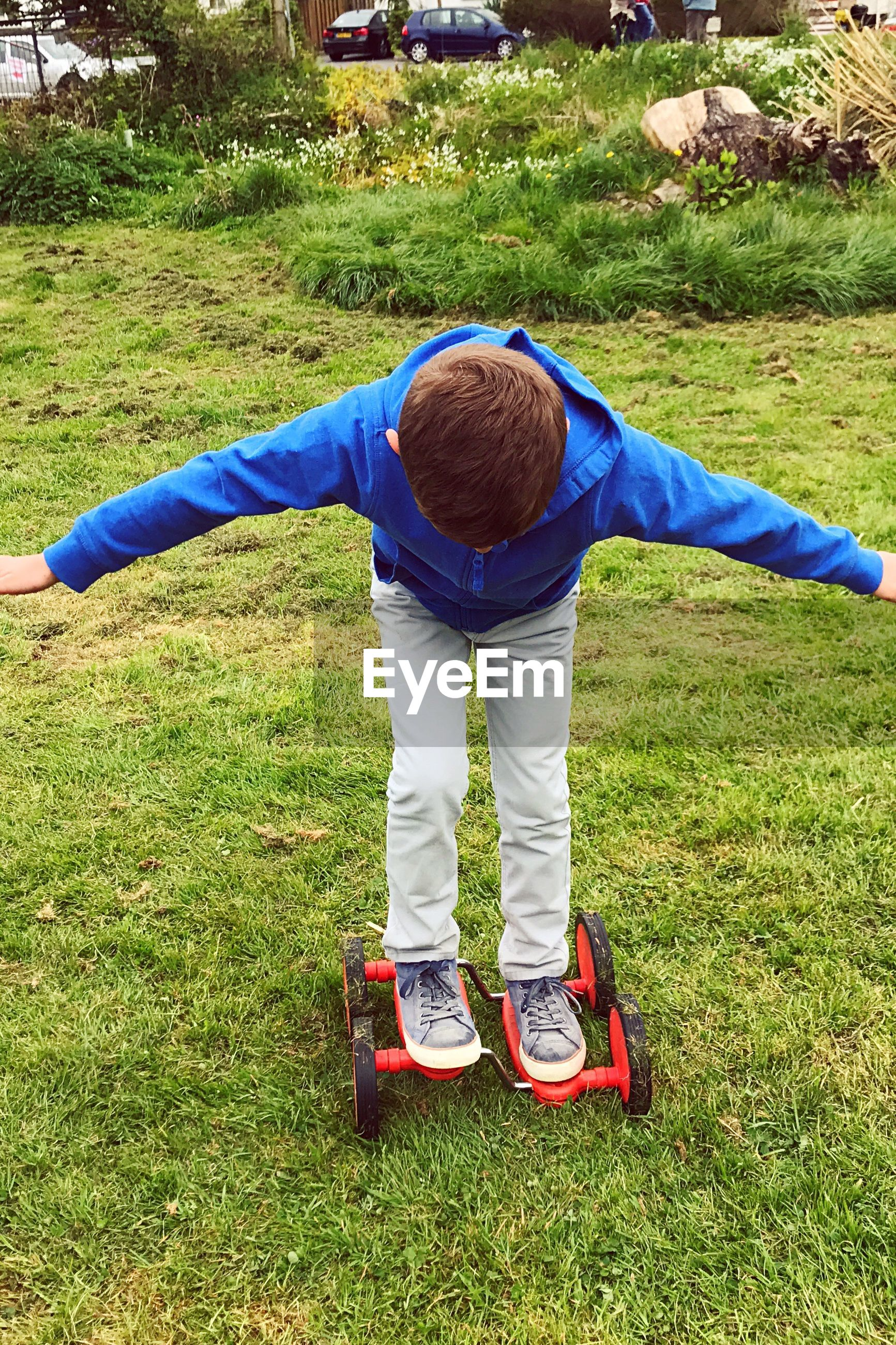 High angle view of boy roller skating on grassy field