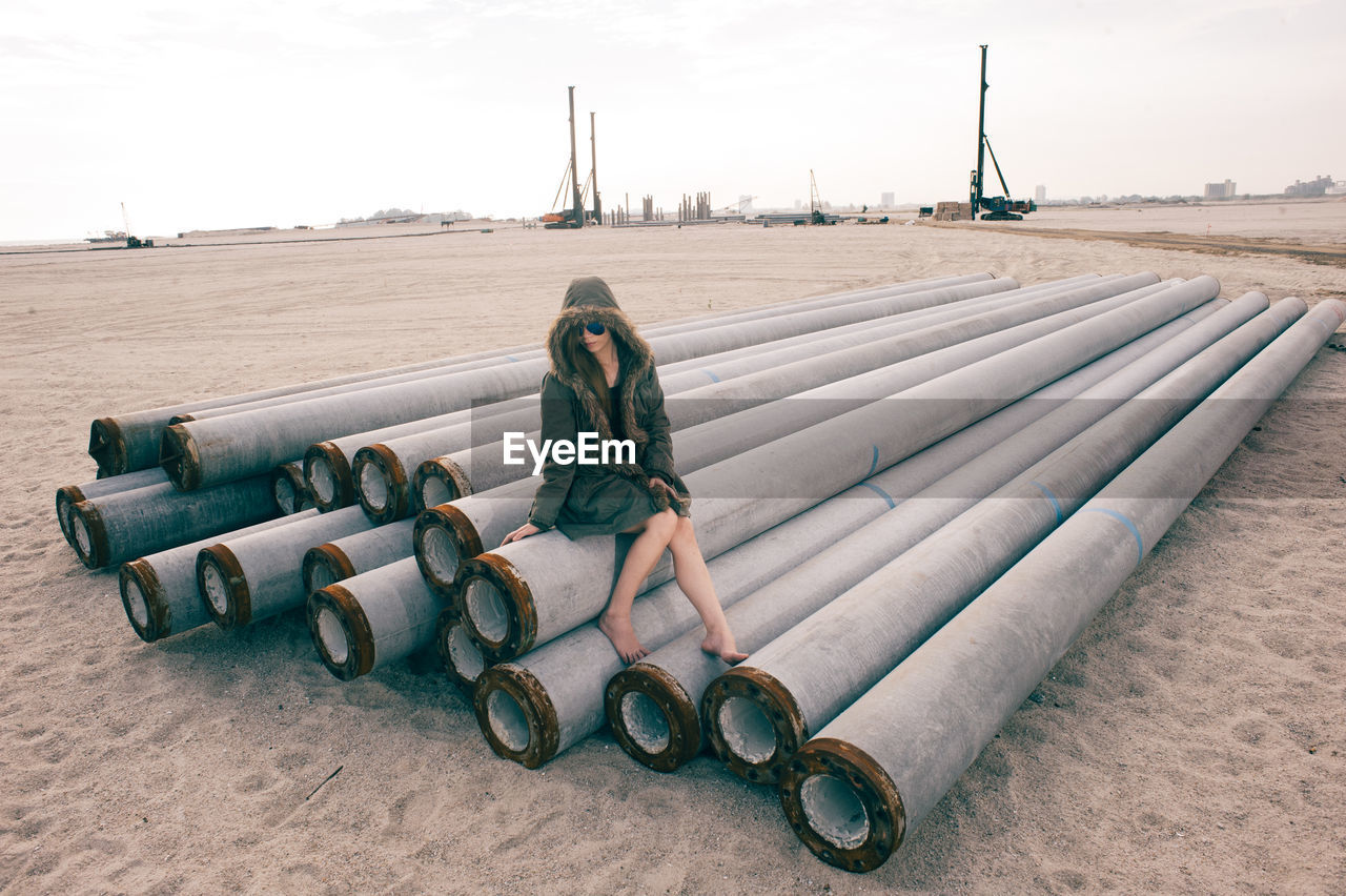 Woman sitting on metallic pipes at beach against sky