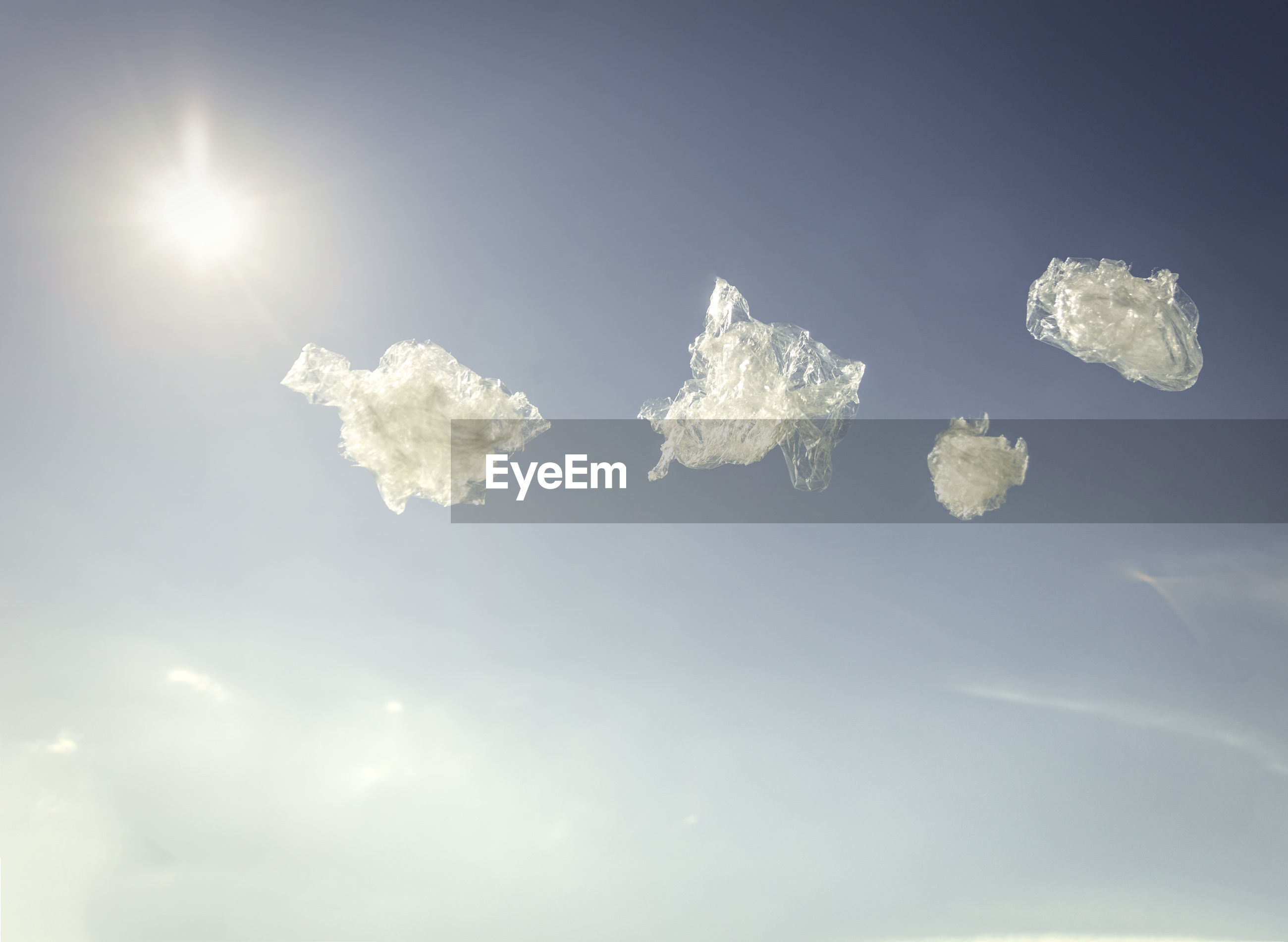 Low angle view of plastic flying against sky during sunny day