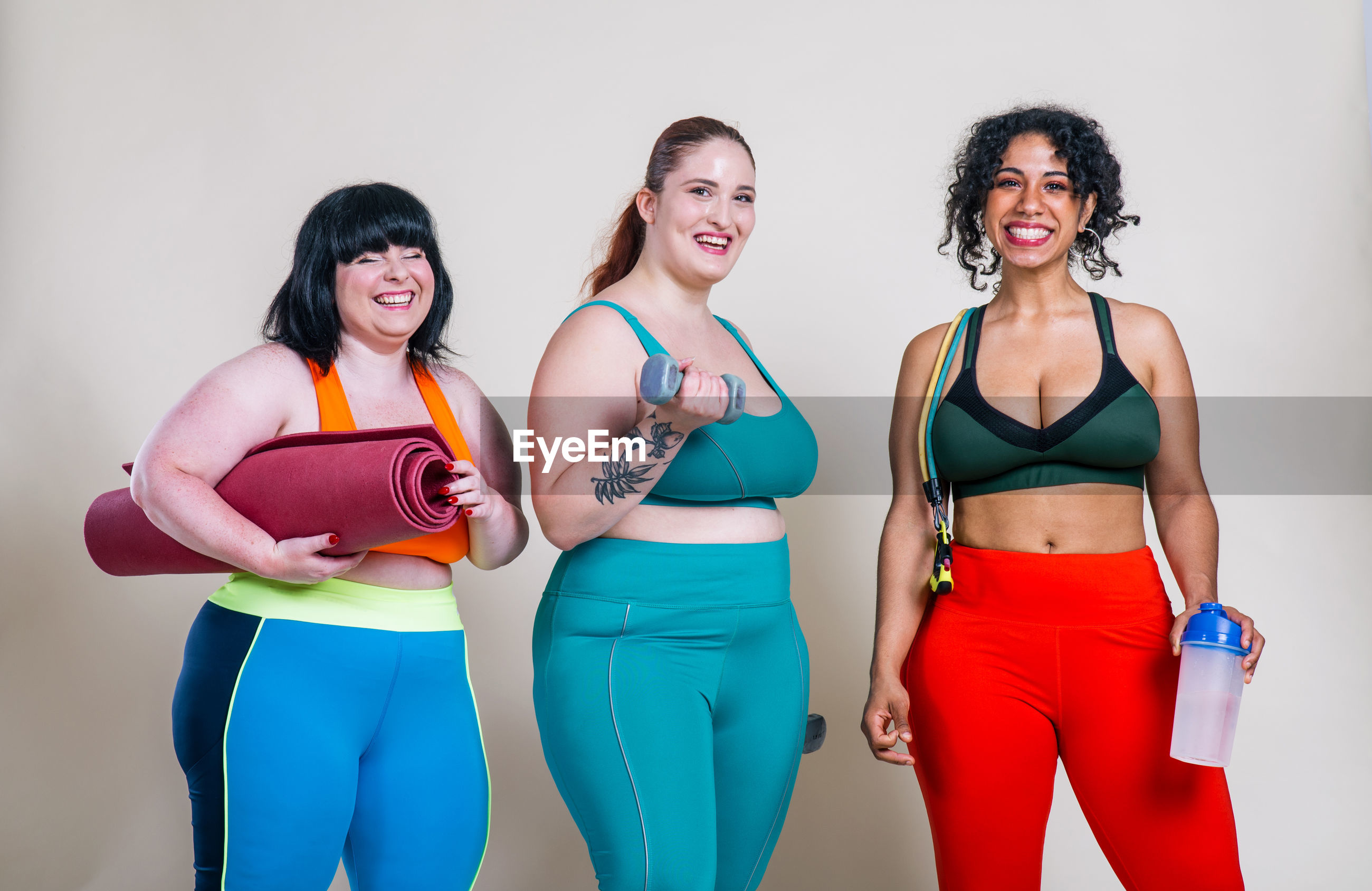 Portrait of happy friends standing against colored background