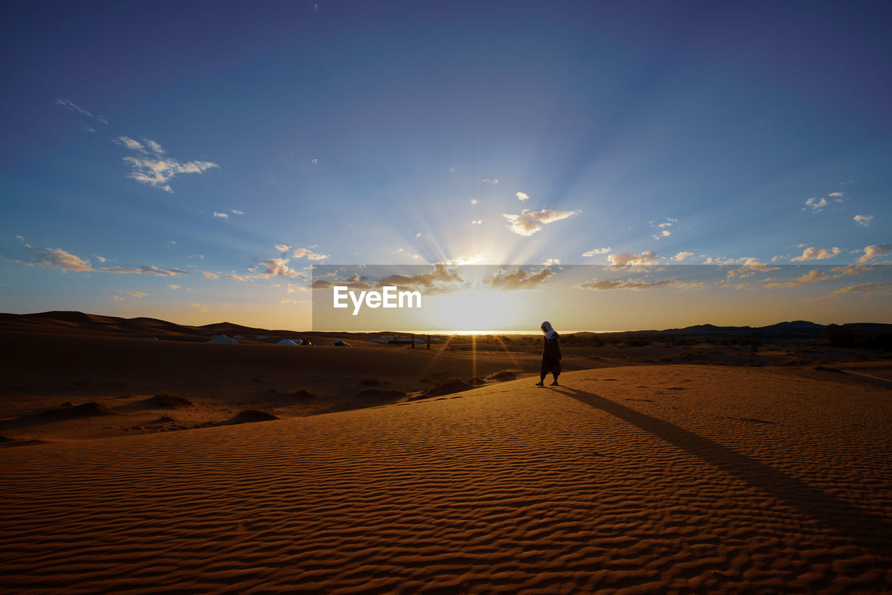 sky, sunset, land, beauty in nature, scenics - nature, tranquil scene, tranquility, sand, sunlight, real people, sun, leisure activity, lifestyles, one person, cloud - sky, nature, non-urban scene, idyllic, landscape, men, lens flare, arid climate, outdoors, climate