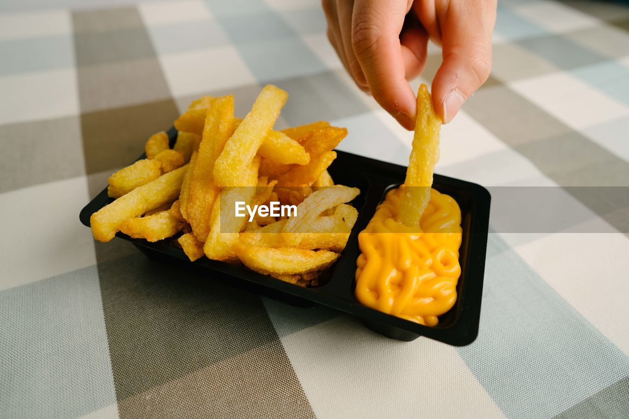 human hand, hand, unhealthy eating, french fries, food, one person, food and drink, fast food, ready-to-eat, human body part, prepared potato, potato, real people, holding, fried, freshness, snack, indoors, unrecognizable person, high angle view, finger, temptation, fast food french fries