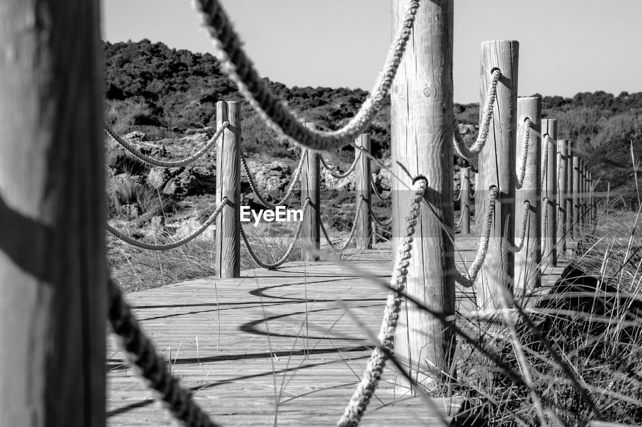 day, metal, no people, sunlight, nature, barrier, fence, security, boundary, protection, rope, land, safety, selective focus, outdoors, wood - material, shadow, post, playground, pole, wooden post