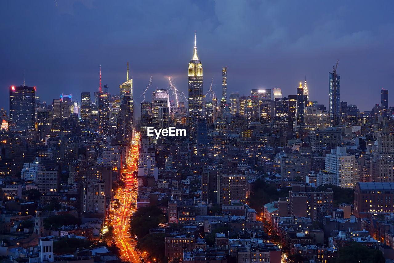 Lighting over illuminated cityscape at night