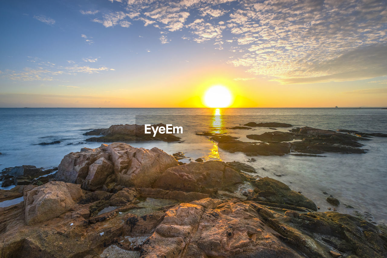 water, sky, sea, beauty in nature, sunset, scenics - nature, horizon over water, horizon, rock, sun, tranquil scene, tranquility, rock - object, solid, beach, land, nature, idyllic, cloud - sky, no people, outdoors, lens flare