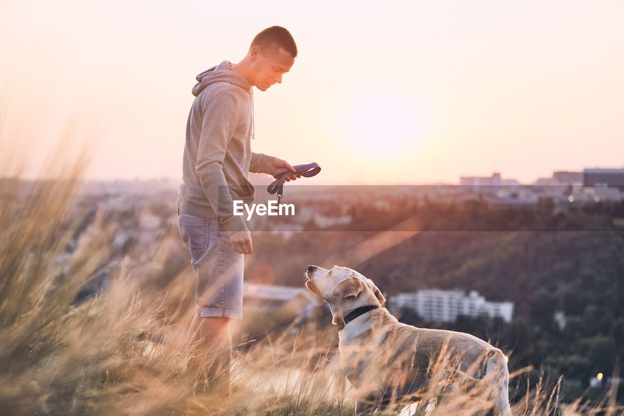 Side View Of Man With Dog Standing On Field Against Sky During Sunset
