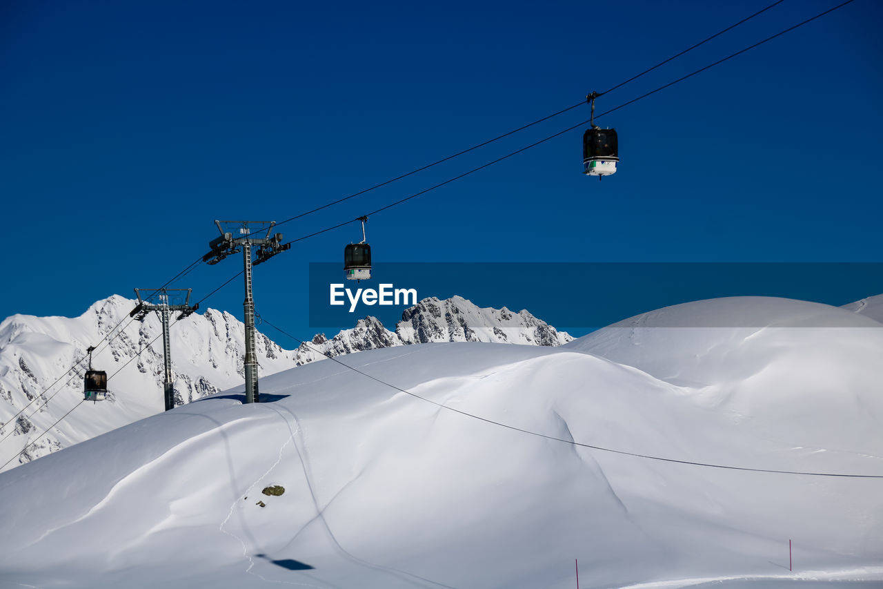 snow, cold temperature, winter, sky, blue, cable, mountain, scenics - nature, cable car, beauty in nature, snowcapped mountain, clear sky, white color, low angle view, nature, overhead cable car, connection, ski lift, day, no people, mountain range, electricity, outdoors