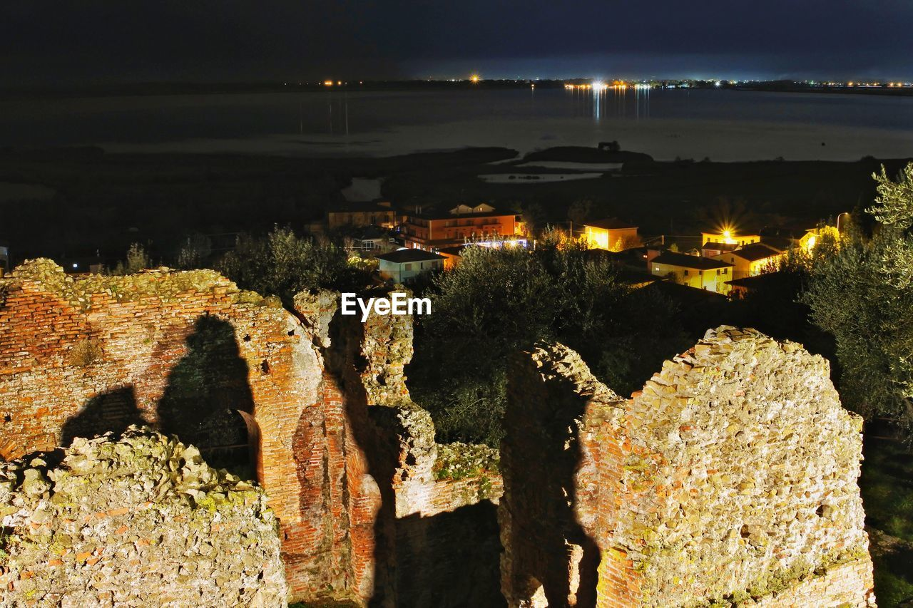 HIGH ANGLE VIEW OF ILLUMINATED ROCKS BY SEA AGAINST SKY