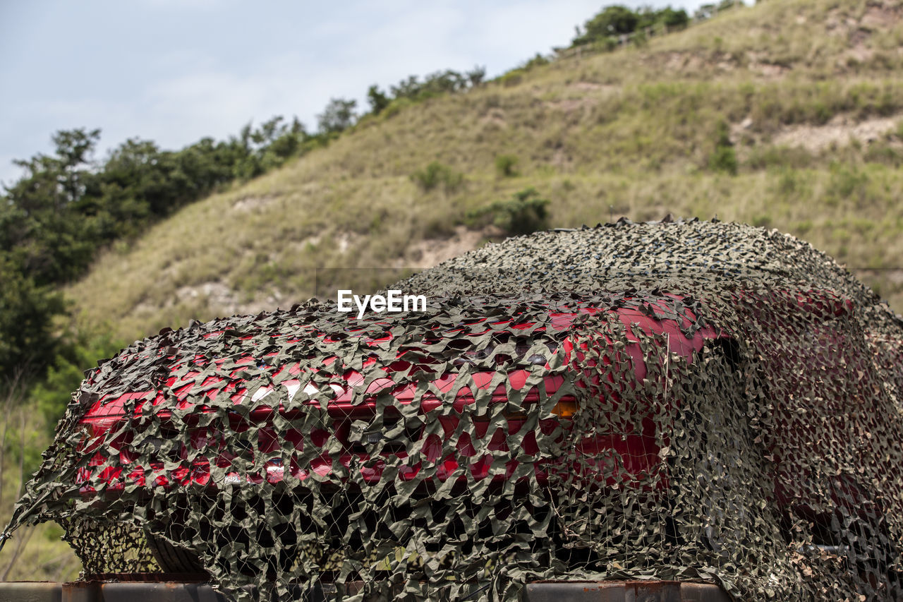 Car Covered With Camouflage Net Against Hill