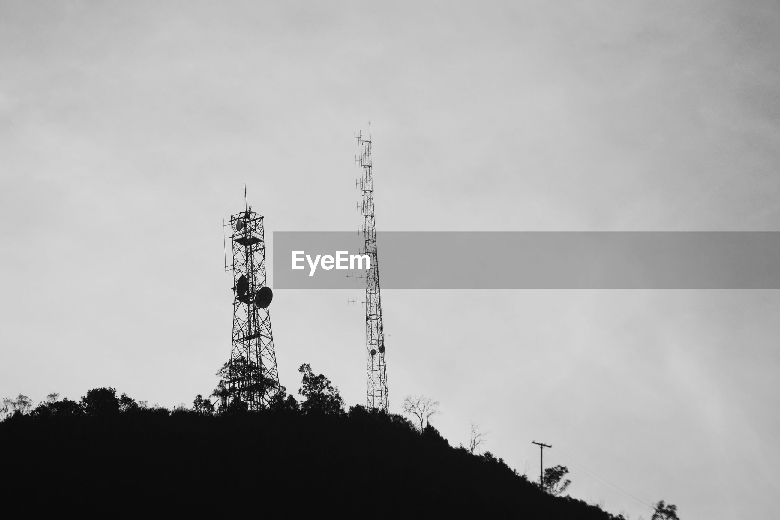 Low angle view of communication towers on mountain against sky