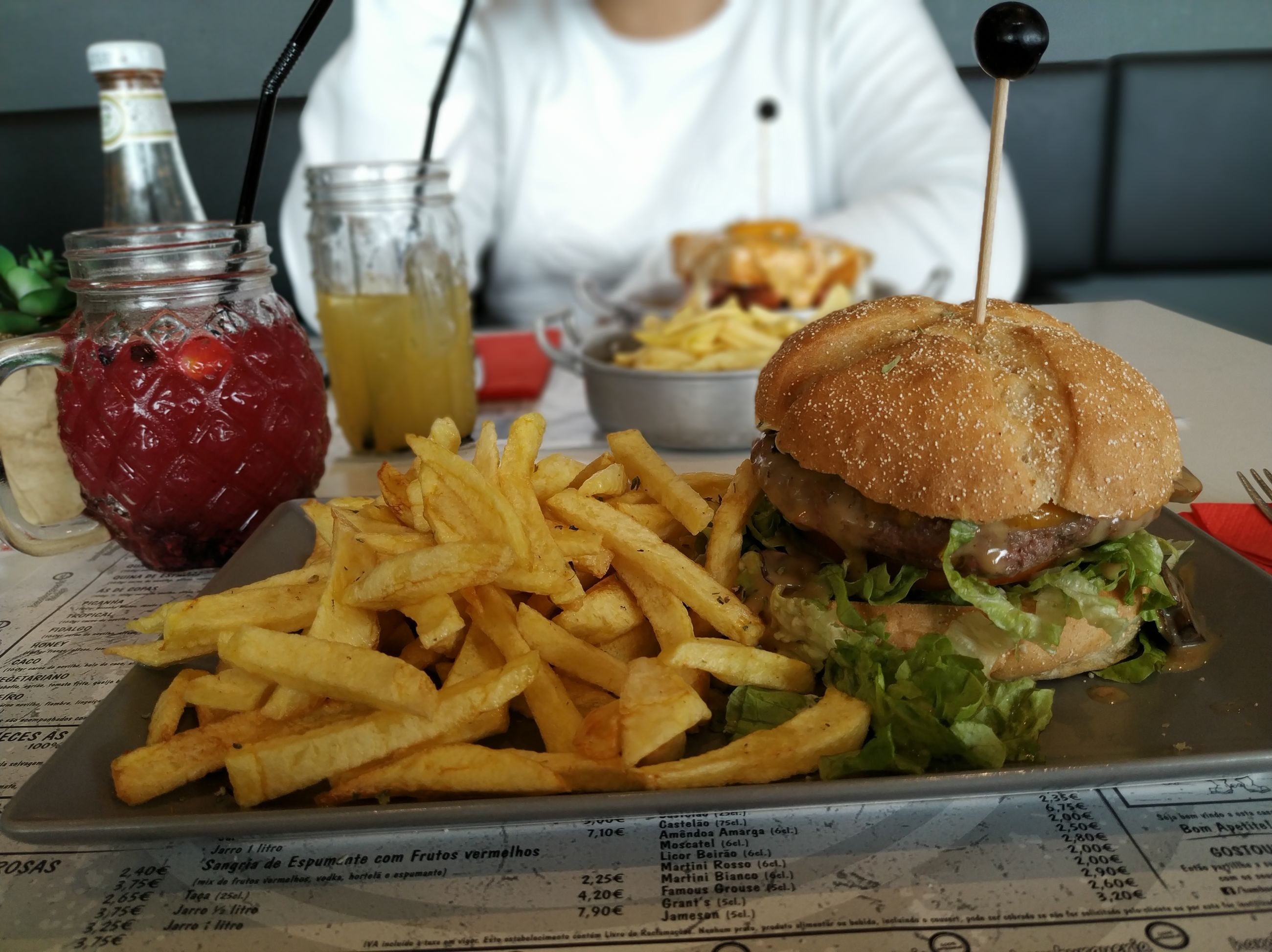 CLOSE-UP OF BURGER AND FRIES ON TABLE