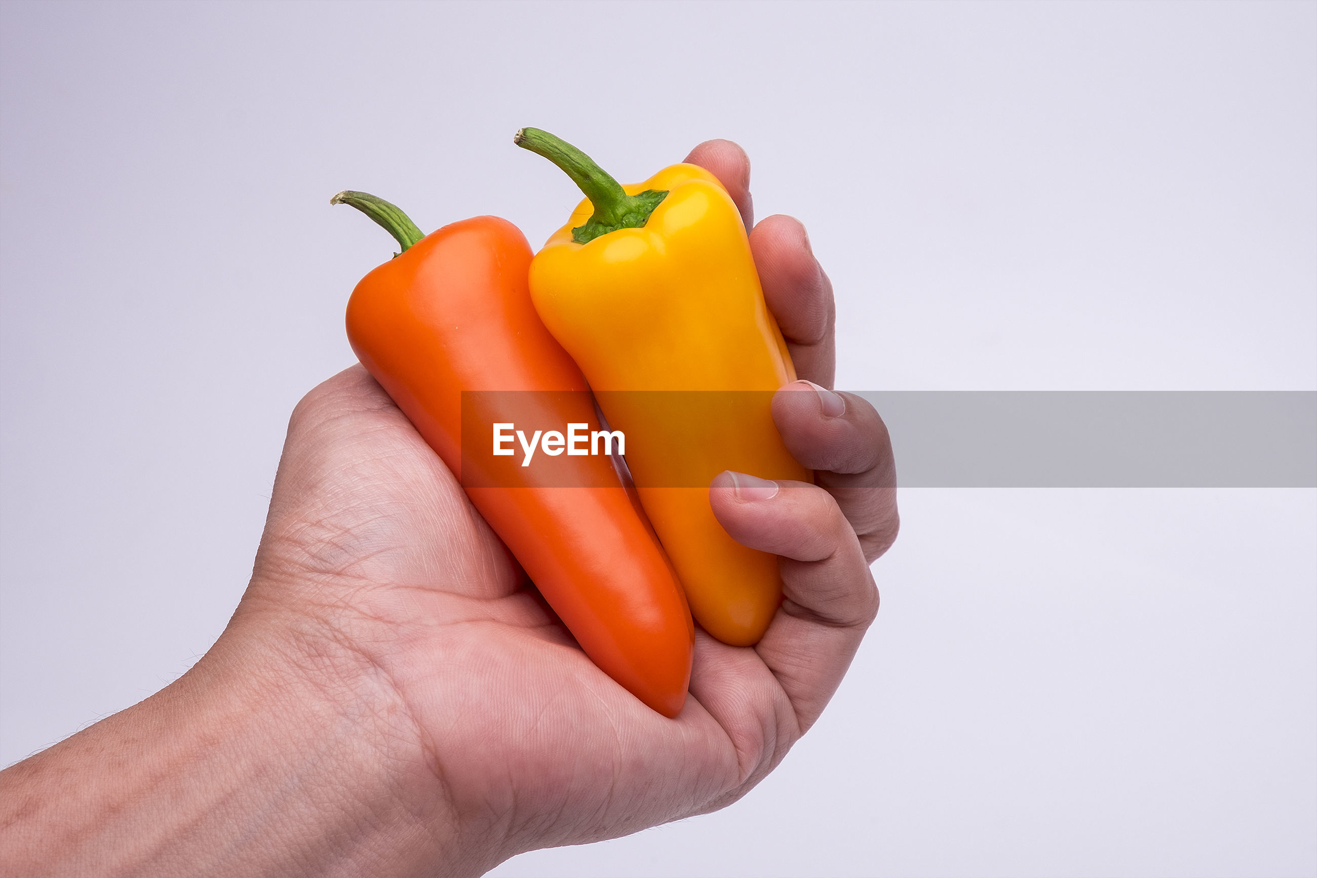 Close-up of hand holding bell peppers against white background