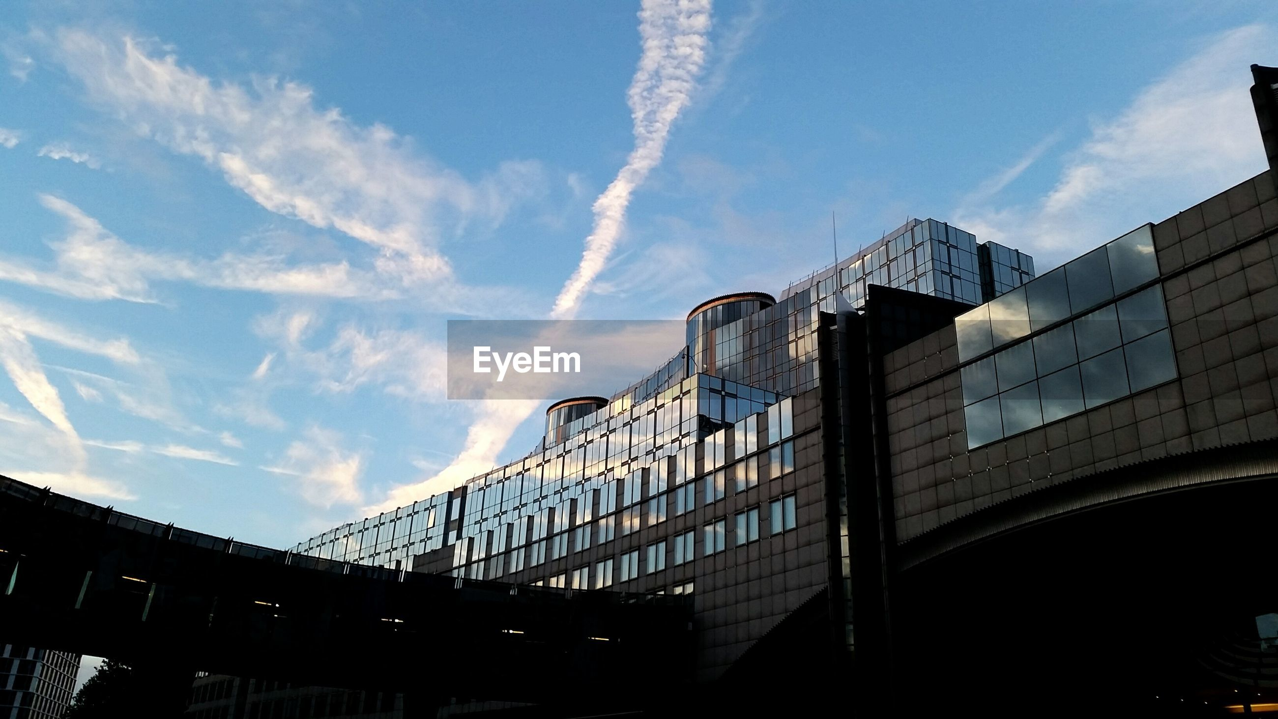 architecture, built structure, low angle view, building exterior, sky, cloud, industry, development, vapor trail, blue, outdoors, industrial building, day, office building, high section, cloud - sky, modern, city life, no people, progress, urban skyline