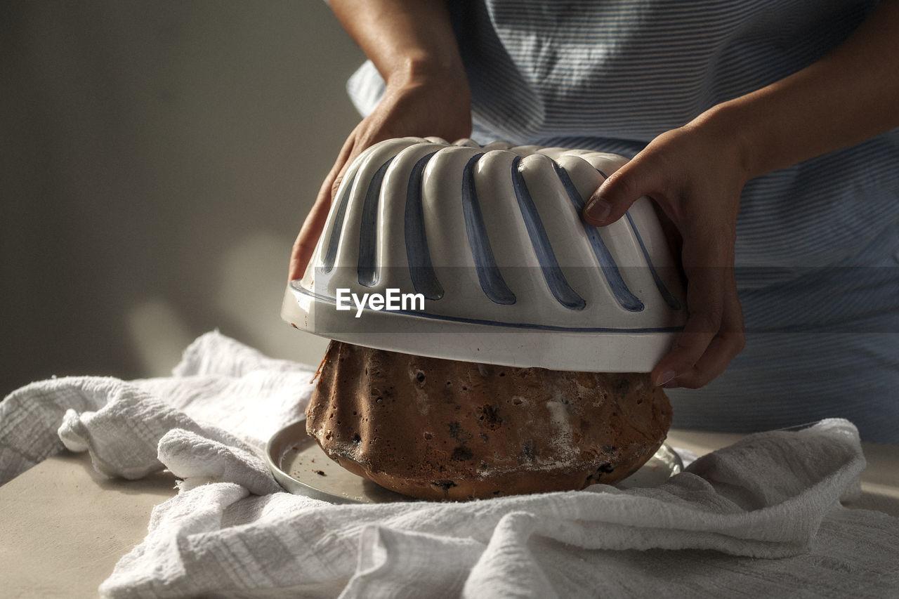 Midsection Of Woman Preparing Bundt Cake