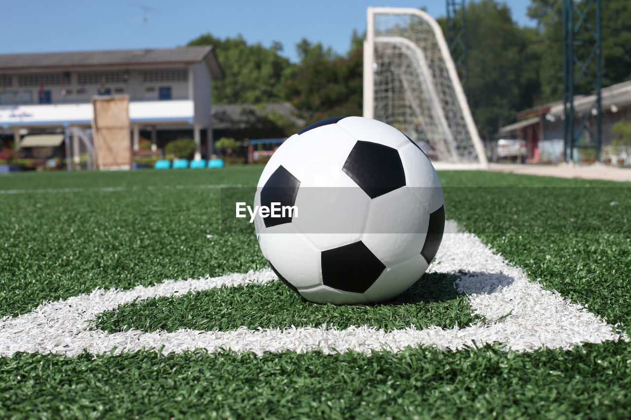 sport, soccer, soccer ball, grass, ball, team sport, sports equipment, soccer field, day, focus on foreground, close-up, plant, no people, playing field, green color, architecture, built structure, outdoors, nature, competition, turf