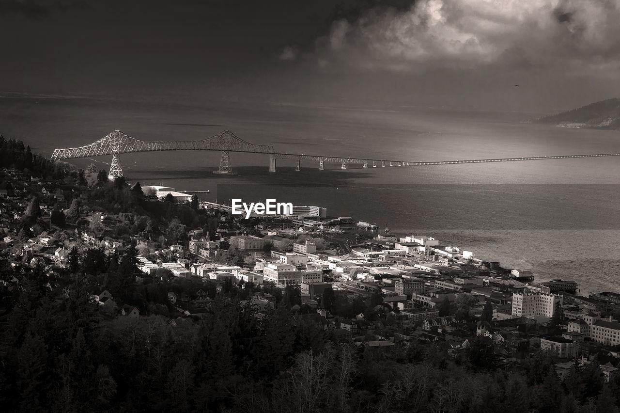Bridge Over Sea In City Against Sky