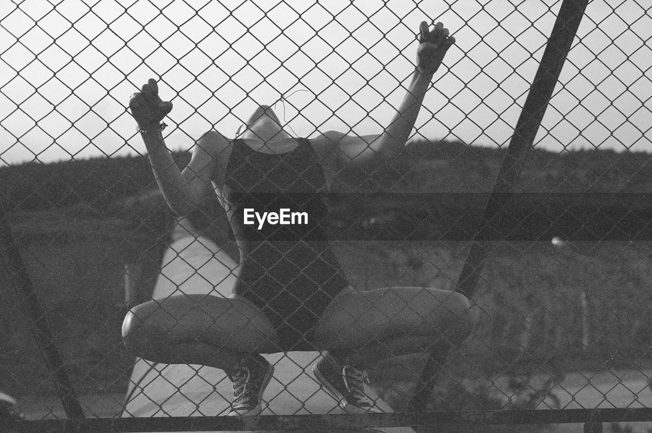 chainlink fence, security, protection, prison, cage, metal, safety, real people, one person, outdoors, day, standing, prisoner, animal themes, sky, playing field, only men, city, full length, nature, adults only, people, one man only, mammal, adult