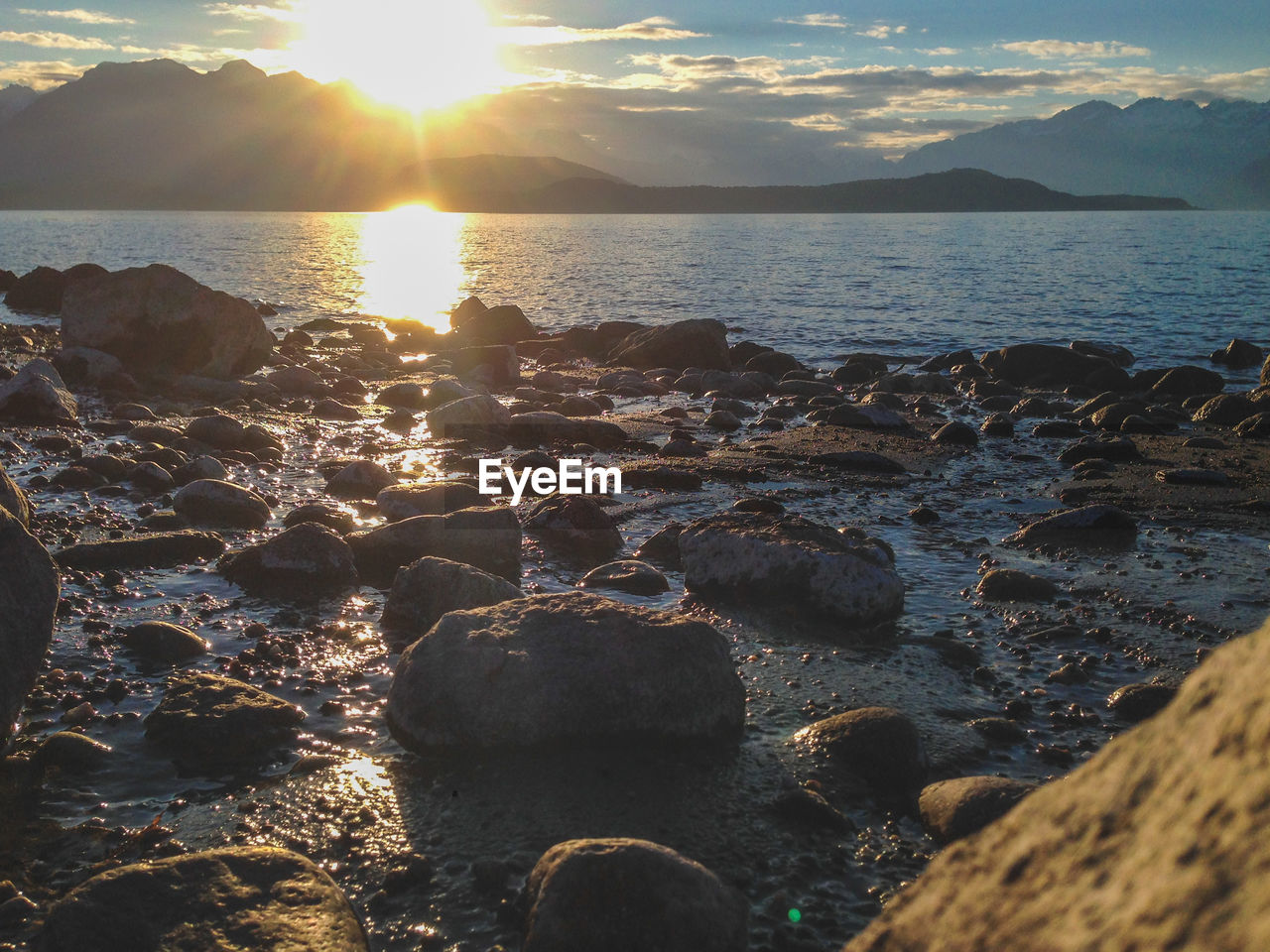 water, sea, sky, beauty in nature, land, sunset, sunlight, beach, rock, tranquility, nature, scenics - nature, solid, rock - object, tranquil scene, sunbeam, no people, sun, idyllic, outdoors, lens flare