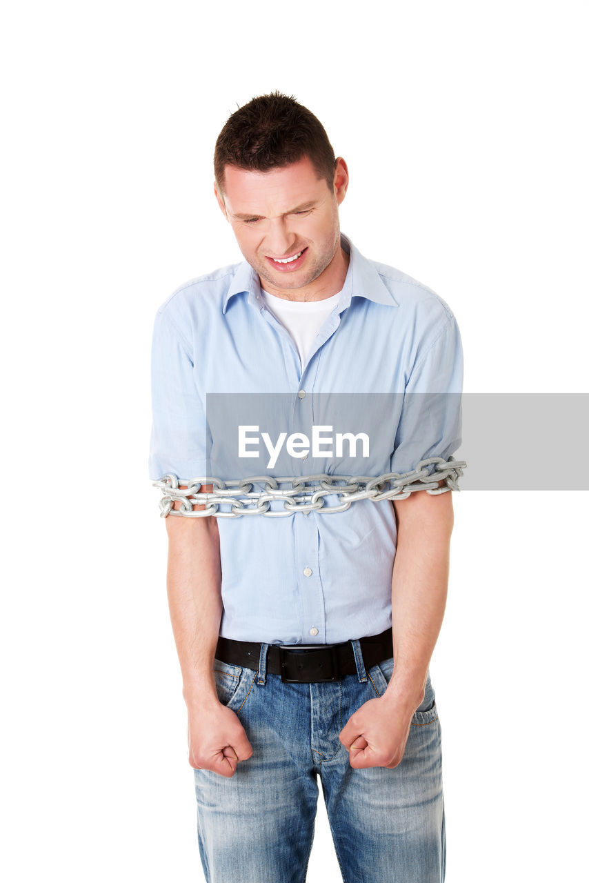 Frustrated man with chains tied up with chain
