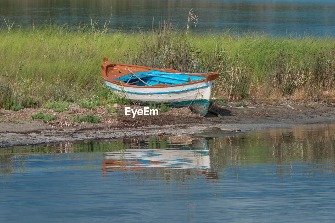 water, reflection, grass, nautical vessel, plant, nature, day, tranquility, transportation, lake, mode of transportation, no people, waterfront, moored, land, tranquil scene, beauty in nature, outdoors, scenics - nature, rowboat