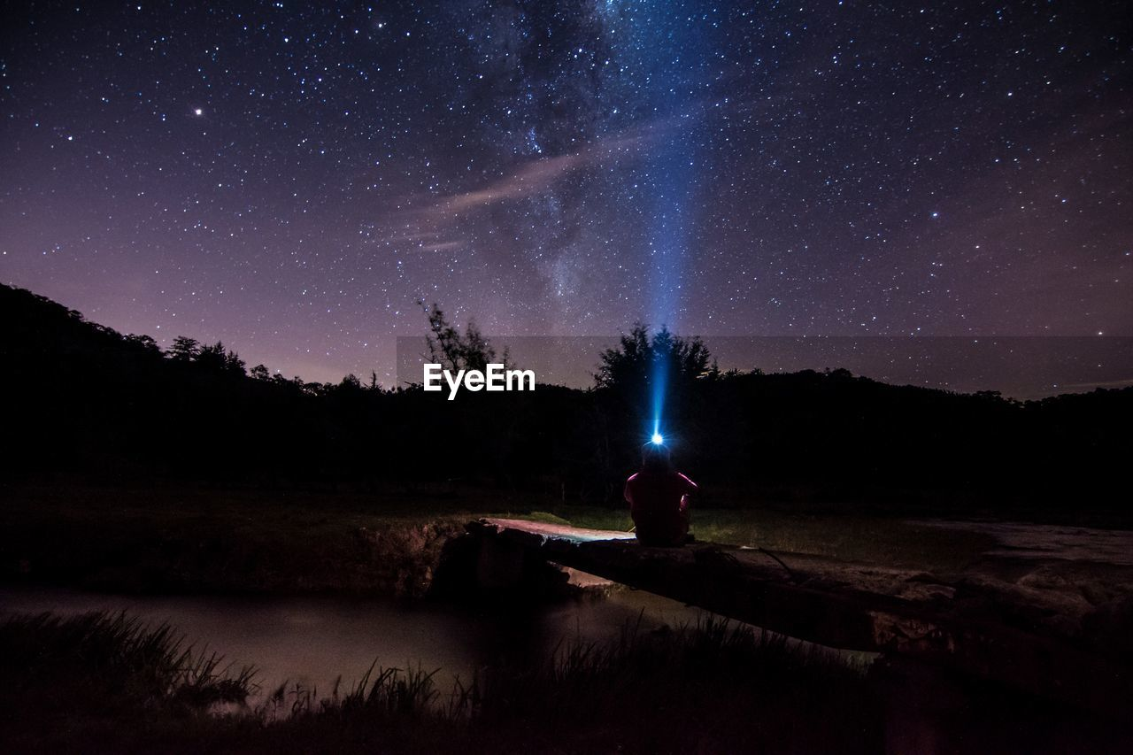Man With Illuminated Headlamp Sitting On Footbridge Against Star Field