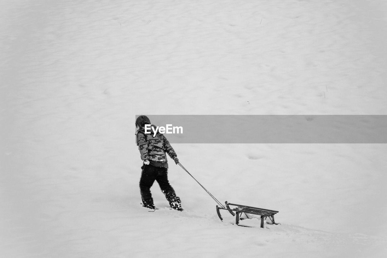 Boy pulling sled on snowy land