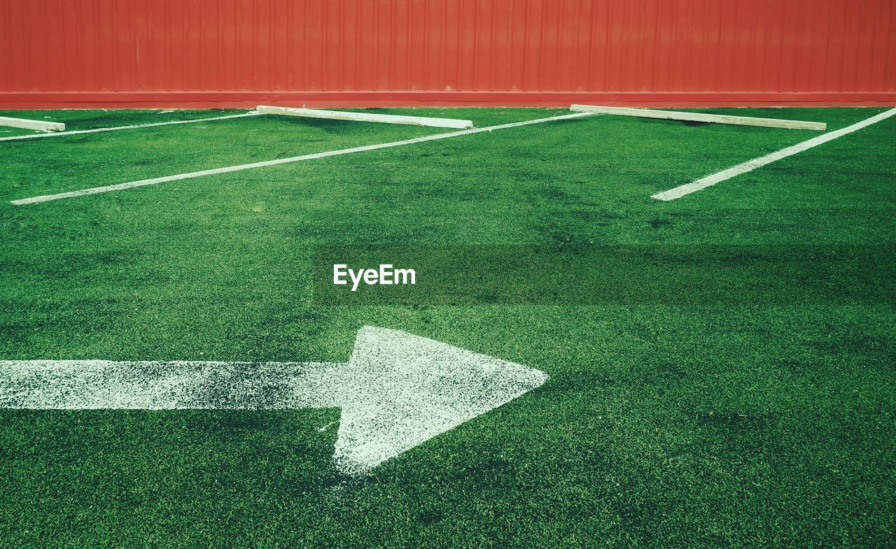 sport, green color, grass, no people, plant, playing field, nature, absence, competition, outdoors, day, empty, arrow symbol, stadium, white color, sign, single line, turf, symbol, marking, yard line - sport